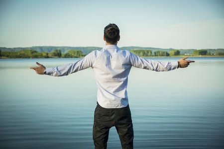 cielos abiertos: Hombre joven en camisa, al aire libre con los brazos extendi� abierta disfrutando de la libertad en frente del lago, vista desde la parte posterior. Foto de archivo
