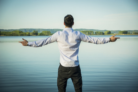 Young man in shirt, outdoor with arms spread open enjoying freedom in front of lake, seen from the back. Standard-Bild