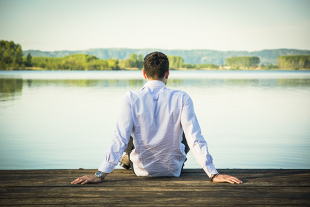 sit: Handsome young man on a lake in a sunny, peaceful day, sitting on a wood pier, thinking or meditating