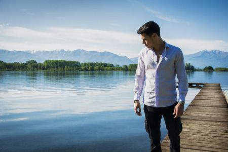 man looking at sky: Handsome young man on a lakes shore in a sunny, peaceful day, standing