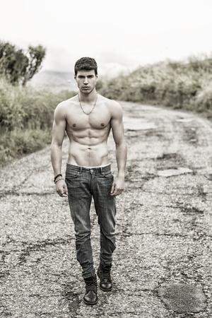 sin camisa: Hombre muscular atractivo descamisado joven en pantalones vaqueros caminando a lo largo de caminos rurales en filtrada, foto insaturado