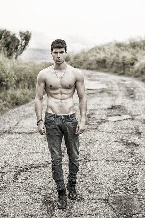 Shirtless sexy muscular young man in jeans walking along rural road in filtered, unsaturated photo