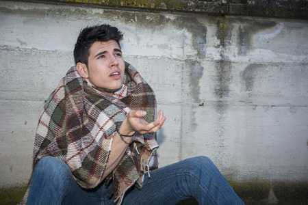 social outcast: Young male beggar on city sidewalk with blanket on his shoulders Stock Photo