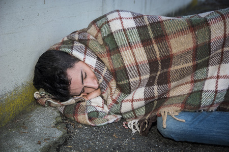 beggar: Young male beggar sleeping on city sidewalk with blanket on his shoulders