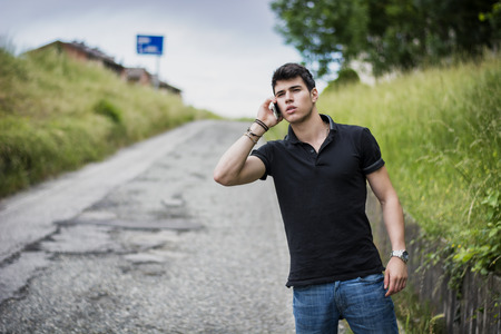 Young handsome man on side of a road, calling on cell phone and waiting for taxi cab