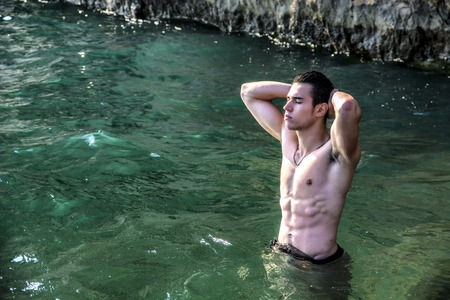 nue plage: Attractive jeune torse nu athlétique homme musculaire debout dans l'eau par la mer ou l'océan rivage, vêtu d'un short, montrant corps musclé
