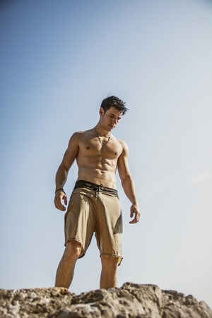 Muscular young man shirtless standing on rock against the sky, seen from below perspective