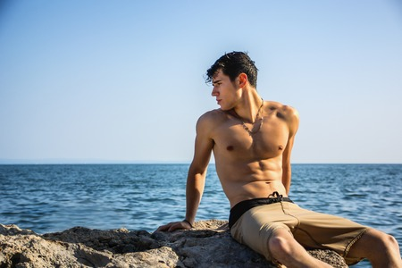 Attractive young shirtless athletic man crouching in water by sea or ocean shore, wearing shorts, looking away to a side