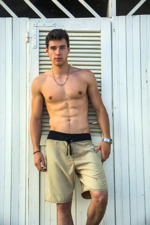 nue plage: Beau et musclé athlétique torse nu jeune homme debout contre plage de sable blanc de changer mur de la salle, l'air confiant à la caméra