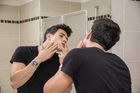 blemishes: Handsome Young Man in Bathroom Touching his Face, Squeezing a Spot or Examining Blemishes