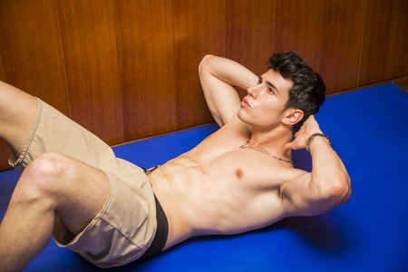 lying on stomach: Attractive blond young man shirtless in gym working out, doing exercises for abs