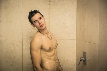 desnudo masculino: Cierre de atractivo joven desnudo Muscular hombre joven que toma la ducha, Mirando a la cámara