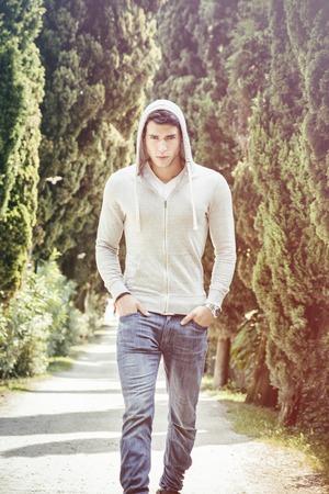 sueter: Apuesto joven caminando a lo largo de caminos rurales con capucha, que parece confidente y relajado