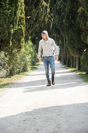 nonchalant: Handsome young man walking along rural road with hoodie, looking confident and relaxed