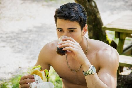 seins nus: Portrait of Young Muscular Man Sitting Shirtless in Park at Picnic Table Eating Fast Food Lunch - Burger, Fries