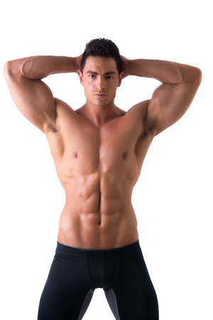 nude abs: Muscular young man standing and looking at camera smiling, shirtless, wearing tight black shorts