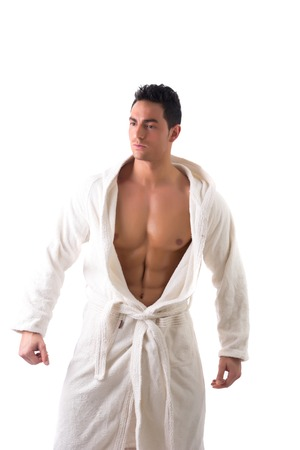 pecs: Handsome young muscle man wearing white bathrobe, keeping it open on muscular torso and pecs, isolated on white background Stock Photo