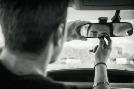 mirror?: Hombre hermoso joven en su coche ajustando retrovisor durante días