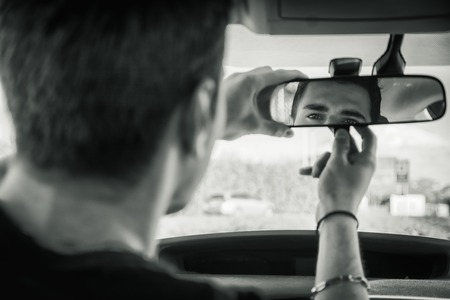 man rear view: Young handsome man in his car adjusting rear view mirror during day Stock Photo