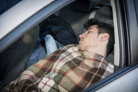 Young handosme man sleeping inside his car, exhausted, tired photo
