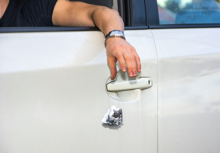 car door: Detail of Man Wearing Wrist Watch Tossing Crumpled Ball of Refuse Out of Car Window onto Ground, Close Up of Irresponsible Man Littering Garbage from Car
