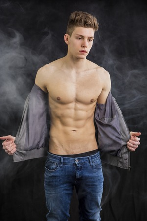 undressing: Attractive trendy athletic fit young man undressing, taking off t-shirt, on dark smoky background Stock Photo