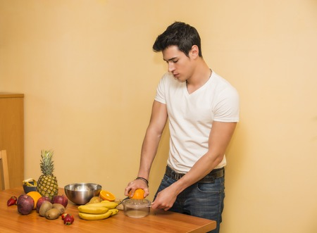 Young man preparing a healthy fruit salad or smoothie, standing leaning on a kitchen counter loaded with an assortment of fresh tropical fruit ,looking down photo