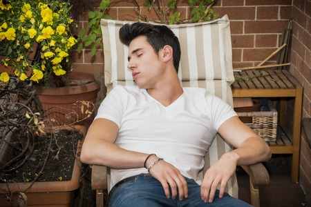 v neck: Handsome young man in balcony sleeping on chair wearing a v-neck white T-shirt while, in summer Stock Photo