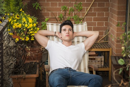 daydreaming: Handsome young man in balcony day-dreaming, sitting on chair wearing a v-neck white T-shirt while, in summer Stock Photo