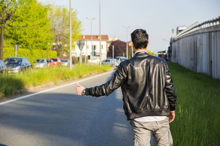 hitch hiker: Back of young man, a hitchhiker waiting for car on roadside in city, wearing black leather jacket Stock Photo