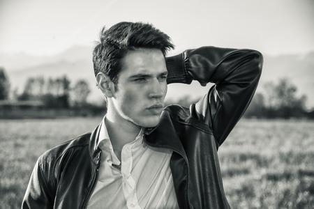 poses de modelos: Hombre hermoso joven en el campo, en frente del campo o pastizales, vistiendo camisa blanca y chaqueta, mirando a otro lado a un lado Foto de archivo