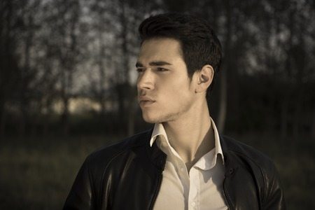 night shirt: Handsome young man at countryside at night or late evening, in field or grassland, wearing white shirt and jacket, looking away to a side Stock Photo