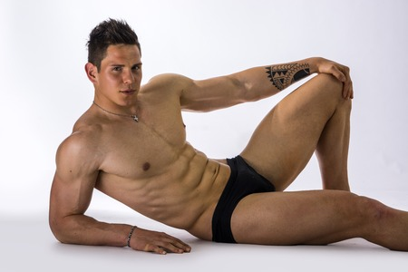Handsome young bodybuilder laying down on the floor, showing ripped abs, muscular pecs, arms Stock Photo