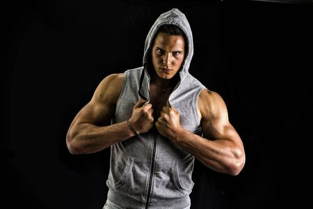 Muscular man with blue hoodie on bare chest, isolated on black background photo