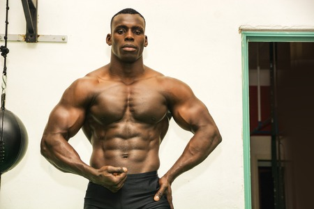 naked black men: Attractive hunky black male bodybuilder doing bodybuilding pose in gym