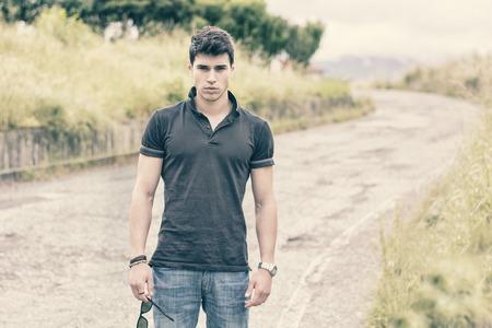 de vaqueros: Apuesto joven atractiva en pantalones vaqueros y camiseta negro caminando a lo largo de caminos rurales