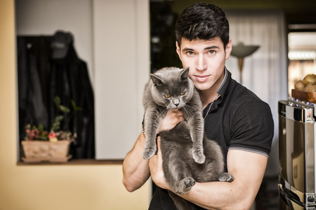 hunter man: Handsome Young Animal-Lover Man Inside the House, Hugging his Gray Domestic Cat Pet. Stock Photo