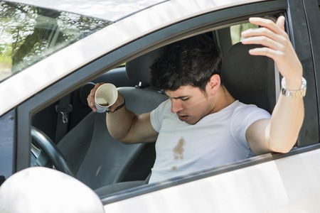 apparel: Young Man Having a Bad Day, Distracted Driver Looking Down in Frustration at Spilled Coffee on White T-Shirt While Sitting in Drivers Seat of Car Stock Photo