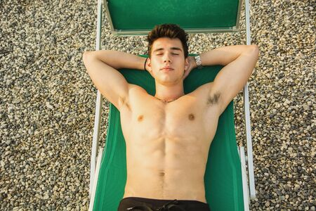 topless model: Shirtless Young Man Drying Off in Hot Sun, Muscular Man Wearing Bathing Suit  Sunbathing on Beach Lounge Chair on Grass Stock Photo
