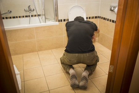 Rear View of a Drunk Young Man Vomiting in the Toilet at Home While in Kneeling Position. Stock Photo