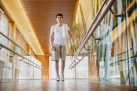 hand rail: Low Angle View Full Length of Young Man with Towel Over Shoulder Standing in Bright Modern Hallway Holding on to Hand Rail