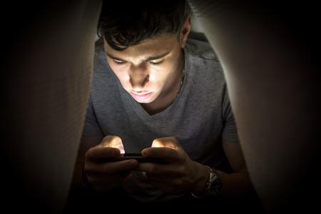 Tiener zichzelf verstopt onder een deken terwijl het gebruik van een mobiele telefoon voor het surfen op internet of chatten online particulier