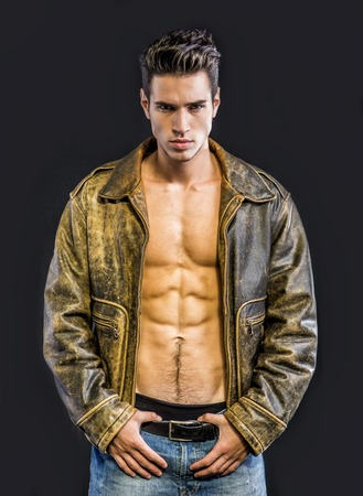 Handsome young man wearing leather jacket on naked torso, isolated on black background looking at camera