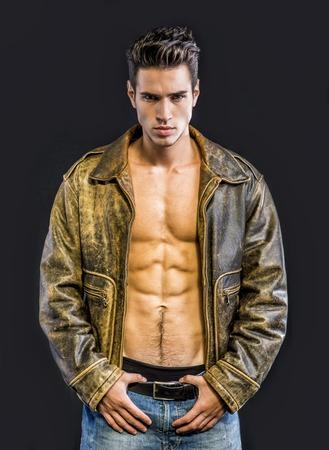 nackt: Gut aussehender junger Mann in Lederjacke auf nackten Oberk�rper, isoliert auf schwarzem Hintergrund Blick in die Kamera