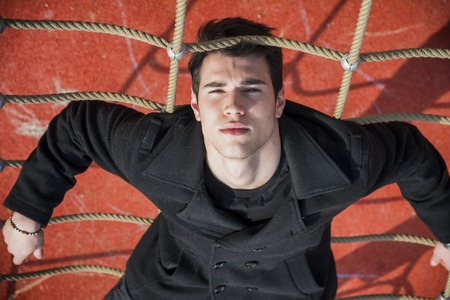 dark haired: Full length of serious dark haired 20s man wearing black jacket and trousers lying upside-down on climbing rope, intensely looking at camera Stock Photo