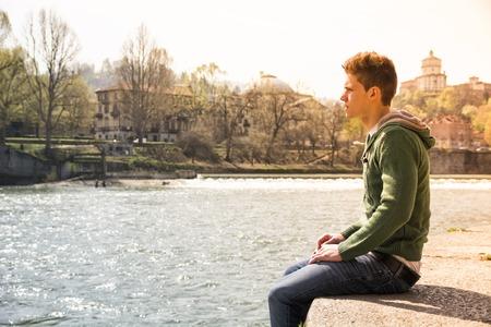 persona sentada: Longitud de tres cuartos de contemplativa luz pelo castaño adolescente vestida de verde con capucha camiseta y denim jeans sentado en la pared al lado pintoresco río en Turín, Italia