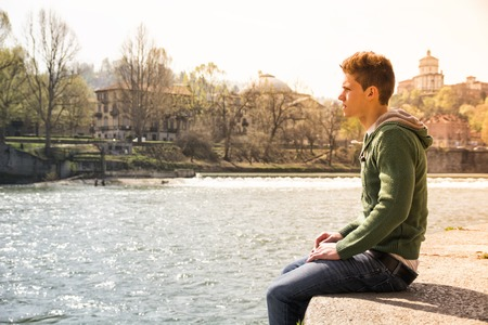 hoodie: Three-quarter length of contemplative light brown haired teenage boy wearing green hooded-shirt and denim jeans sitting on wall beside picturesque river in Turin, Italy