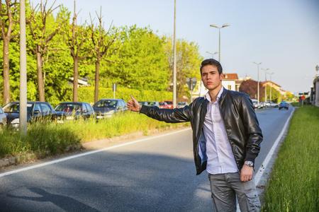 chaqueta de cuero: Apuesto joven, un autoestopista a la espera de coche en carretera en la ciudad, con chaqueta de cuero negro