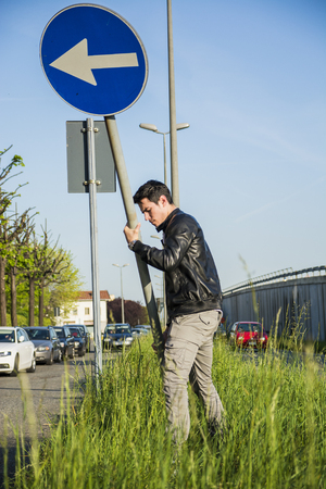 median: Young Man Wearing Leather Jacket Moving Arrow Road Sign in Long Green Grass Median Beside Road