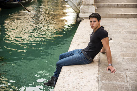 dark haired: Portrait of Attractive Dark Haired Young Man Sitting Docks Next to Narrow Canal in Venice, Italy